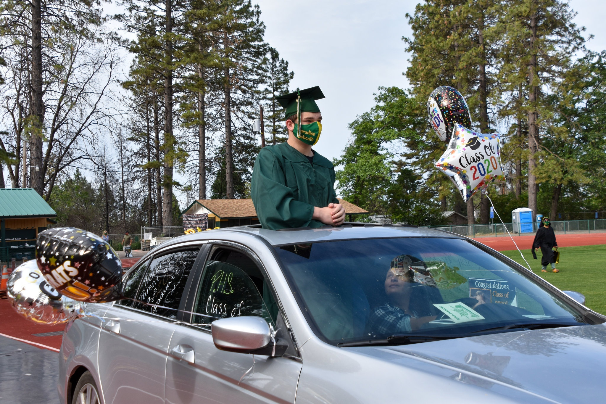 After arriving on Paradise High School's Om Wraith field for the school's first ever drive-in graduation ceremony, Brian Enright, a senior, takes in the scene. Credit: Anne Daugherty