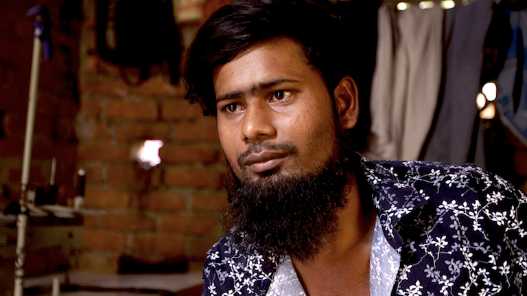"Ramzan, 26, sits in the room where he works, eats and sleeps in Kolkata. Since his family's farm on Mousuni was destroyed by a flood, he has worked as a tailor in the city. Still image from ""Losing Ground."""