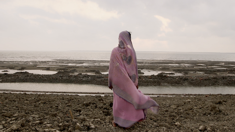 "Geeta regards the rising sea from an embankment. Still image from ""Losing Ground."""